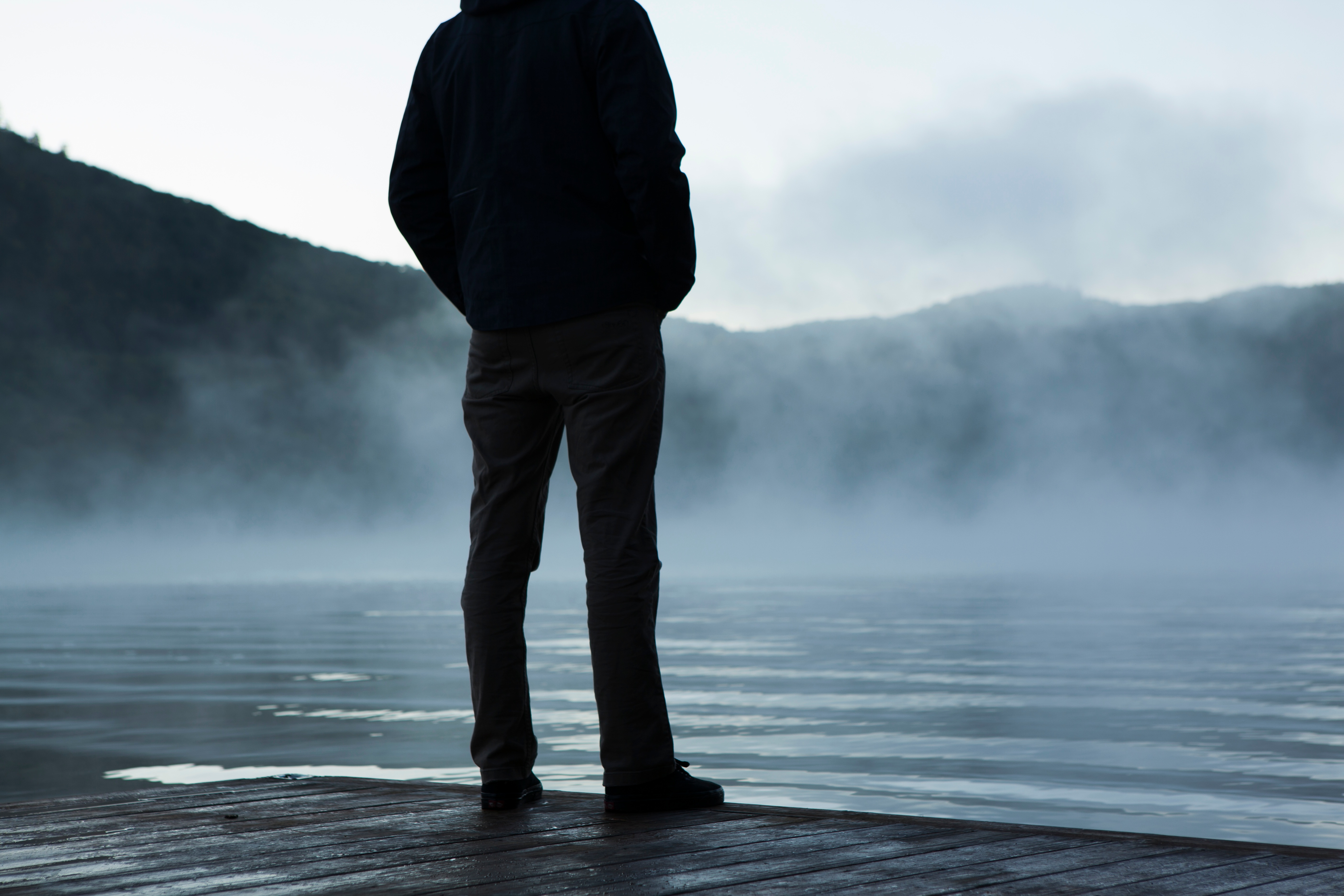 man standing on dock at foggy lake