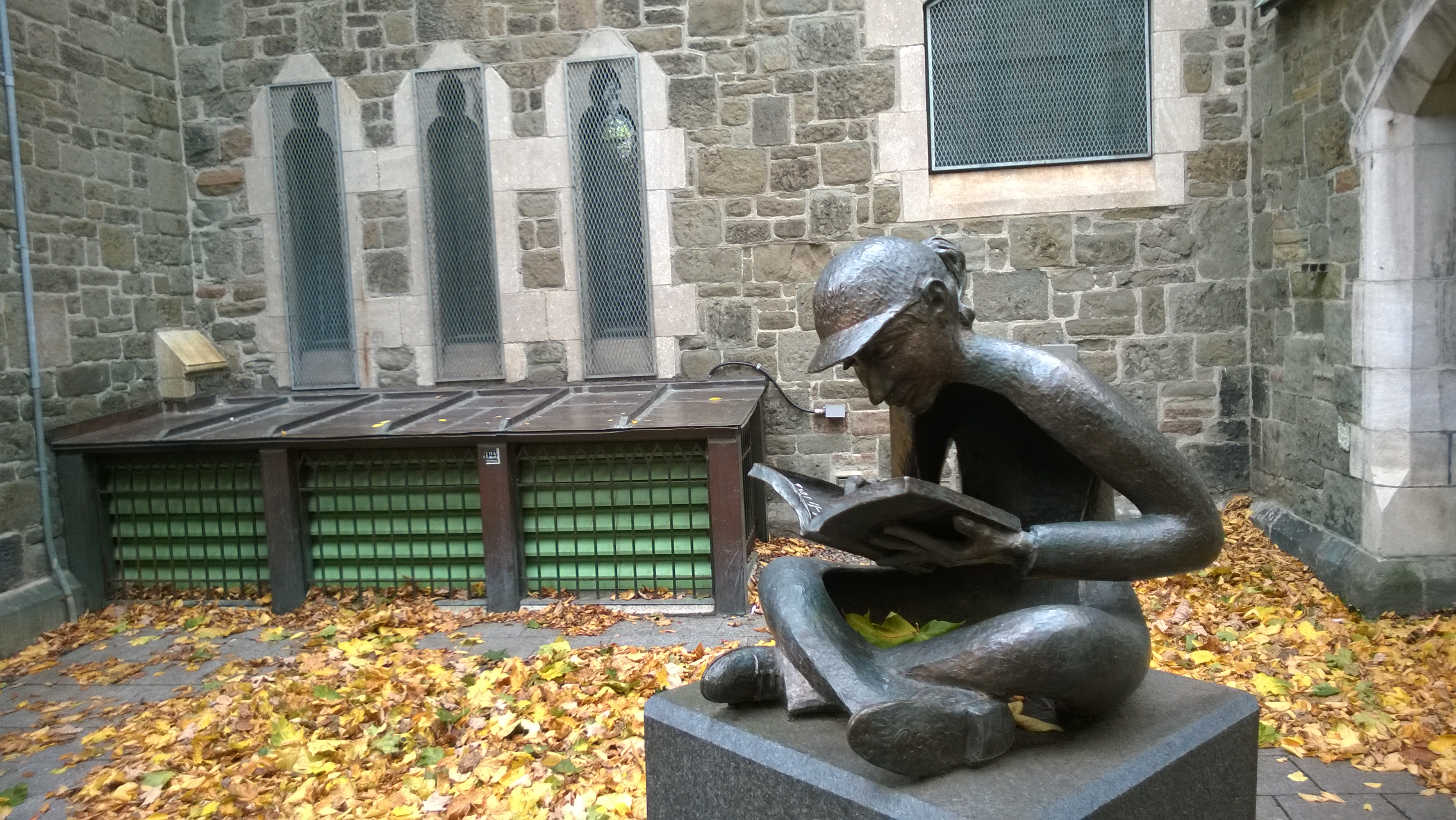 statue of child reading a book