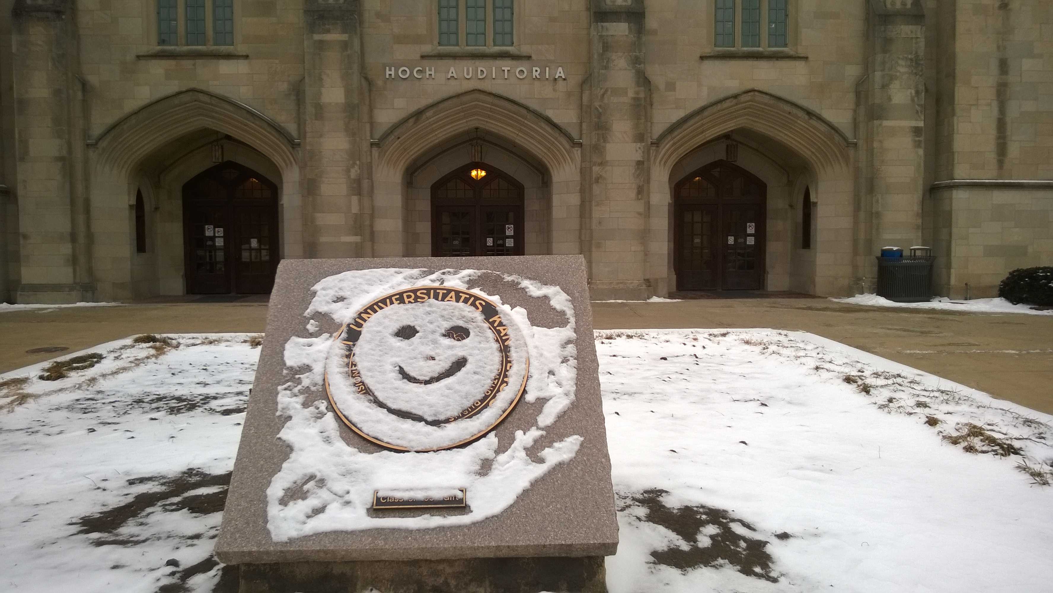 smiley face drawn on snow-covered university seal outside Budig Hall at University of Kansas