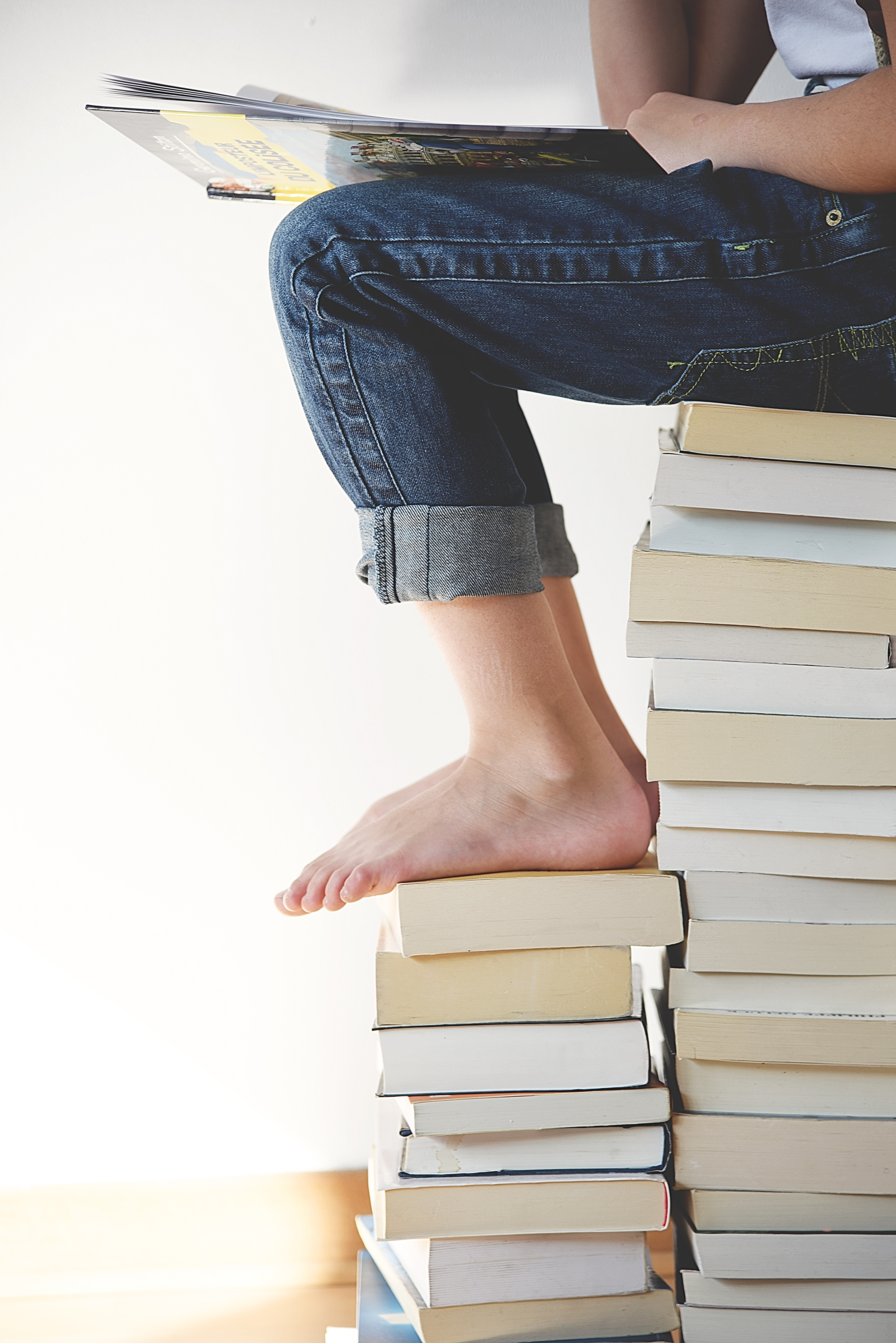 woman sitting on large stack of books