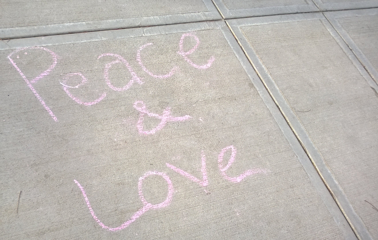 words in sidewalk chalk saying peace & love