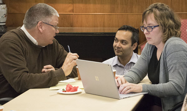 Rajiv Jhangiani kneeling at a table where Carl Luchies and Molly McVeigh from engineering sit