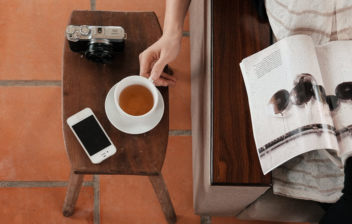 woman reading magazine with phone and coffee on table beside her