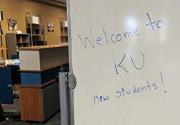 A whiteboard with Welcome to KU, new students written in blue