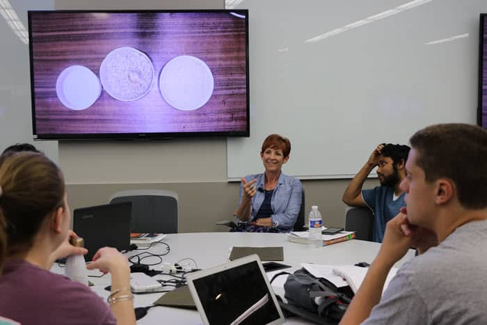 students gather around a round table, with the instructor facing forward. A screen with a PowerPoint slide is behind her.